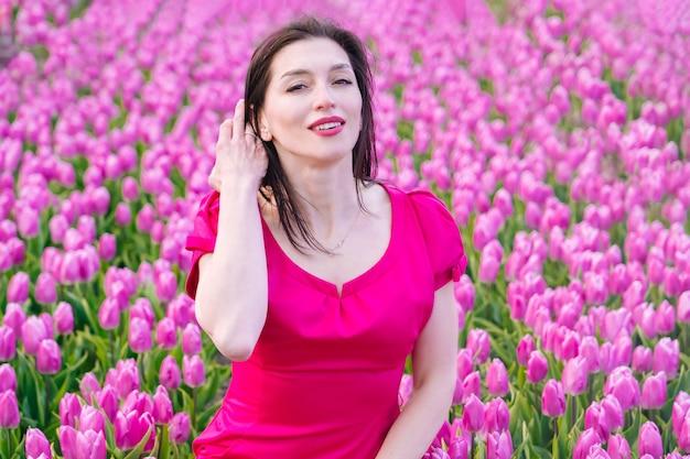 カラフルなチューリップの花畑に立っている夏のドレスの美しい女性