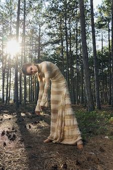 Красивая женщина в солнечном свете сарафана и стройной фигуре деревья лесной природы.
