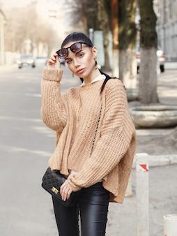 Красивая женщина в солнечных очках и свитере на улице.