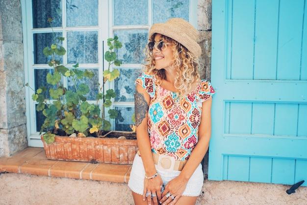 선글라스와 니트 모자를 쓴 아름다운 여성이 집의 닫힌 유리창에 기대어 서 있습니다. 주거용 집에 대해 포즈를 취하는 젊은 백인 여자. 선글라스와 모자에 포즈 hipster 문신된 여자