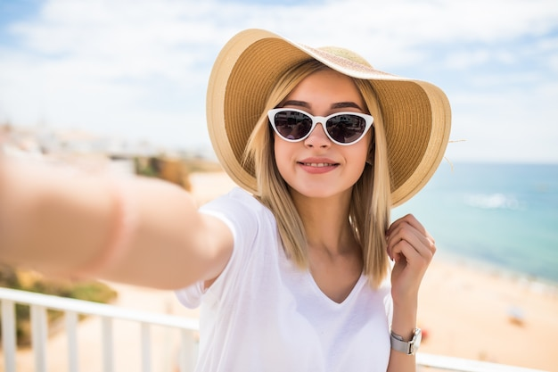 Красивая женщина в солнцезащитных очках и летней шляпе, делающая селфи на пляже