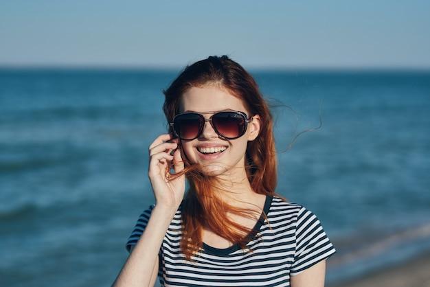 산 빨간 머리 줄무늬 tshirt에서 바다로 선글라스에 아름 다운 여자
