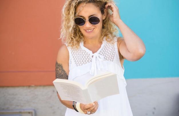 야외에서 벽에 책을 읽고 선글라스를 끼고 있는 아름다운 여성, 백인 여성이 책을 읽고 있습니다. 머리에 손을 얹고 책을 읽는 선글라스를 쓴 행복한 문신한 여자