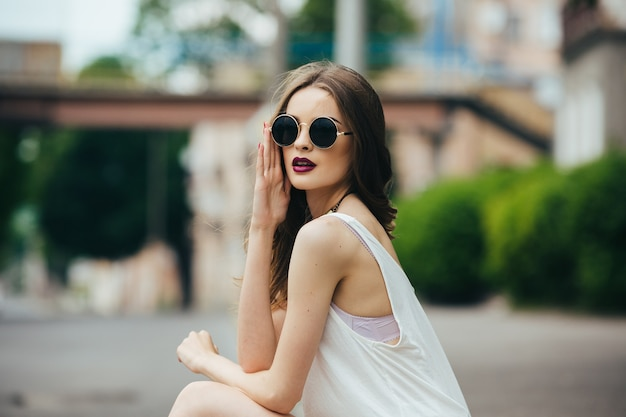 아스팔트에 앉아 선글라스에 아름 다운 여자