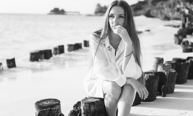 海沿いに座っている水着で美しい女性