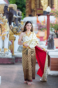 笑顔で寺院に立っているタイの伝統的な衣装の美しい女性