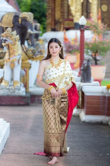 태국 전통 복장 미소하고 사원에 서있는 아름다운 여자