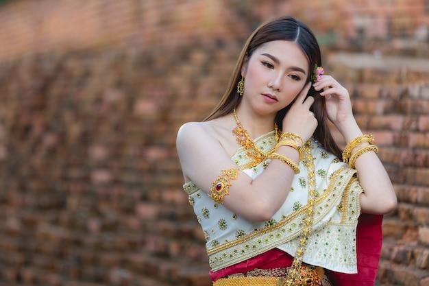 Красивая женщина в традиционном тайском наряде улыбается и стоит в храме