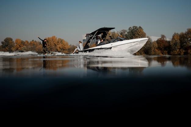 Красивая женщина в черном купальнике катается на вейкборде на высокой волне моторной лодки