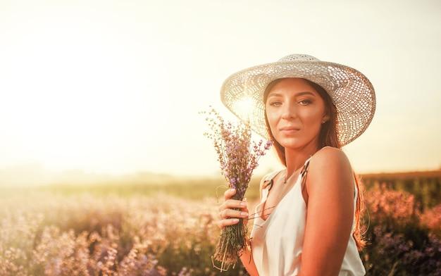 Красивая женщина в поле лаванды на закате. прекрасное летнее настроение.
