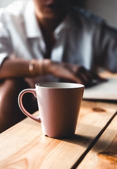 아침에 아름 다운 여자는 커피를 마시고 흰 셔츠에 오래 된 책을 읽습니다. 교육, 마셔.