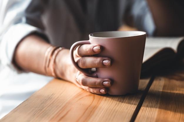 아침에 아름 다운 여자는 커피를 마시고 흰 셔츠에 오래 된 책을 읽습니다. 교육, 술.