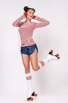 Красивая женщина в роликовых коньках и с красными наушниками