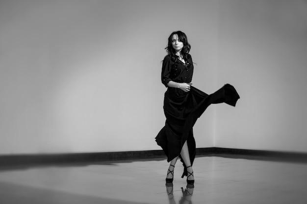 Красивая женщина в комнате в студии танцует в черном платье с длинными темными кудрями на голове