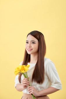 黄色の背景に手に花ガーベラと白いシャツの美しい女性。彼女は微笑んで笑う