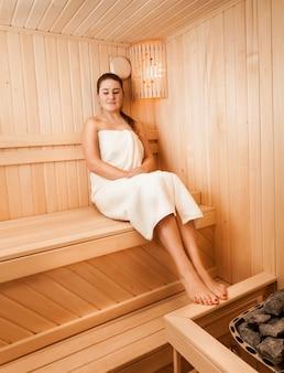 Красивая женщина в полотенце, сидя на скамейке в сауне рядом с духовкой