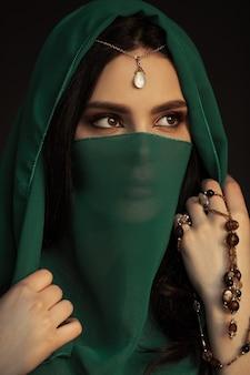 伝統的な衣装の美しい女性。暗い背景に対して屋内に立っている伝統的な宝石を身に着けている完璧な明るい化粧をした少女のスタイリッシュな肖像画。目をそらしているモデル