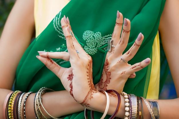 헤나 문신 보석 팔찌와 전통적인 이슬람 인도 결혼식 녹색 사리 드레스 의상에서 아름 다운 여자는 손을 nritta odissi samyuta hasta mudras 댄스 운동 조류 개념 배경