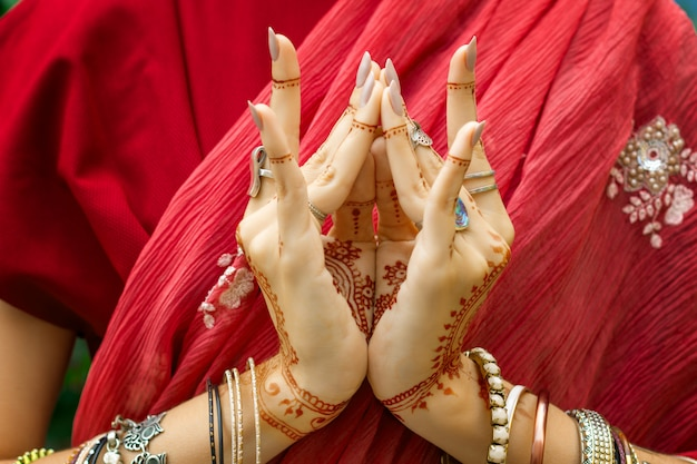 Красивая женщина в традиционном мусульманском индийском свадебном розово-красном платье с татуировкой хной, браслеты с украшениями делают руки nritta odissi samyuta hasta mudras танцуют движение лотоса бутон цветка концепция фон