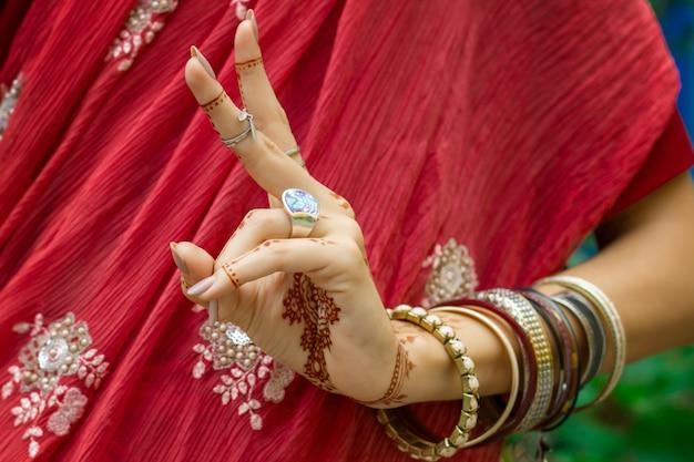 Красивая женщина в традиционном мусульманском индийском свадебном розово-красном платье сари с татуировкой хной, браслеты с украшениями делают руки nritta odissi samyuta hasta mudras dance движение kartarimukha концепция фон