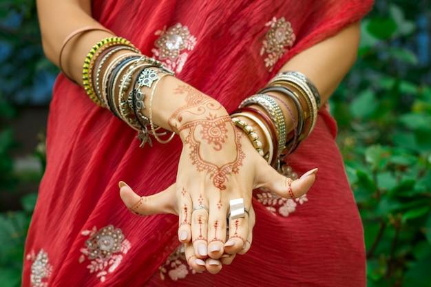 Красивая женщина в традиционном мусульманском индийском свадебном розово-красном платье сари с татуировкой хной, браслетами делают руки nritta odissi samyuta hasta mudras dance движение matsya fish концепция фон