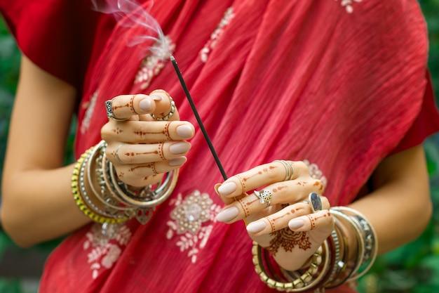 Красивая женщина в традиционных мусульманских индийских свадебных розовых сари одевает руки с татуировкой хной. украшения и браслеты mehndi держат горящие ароматические палочки.