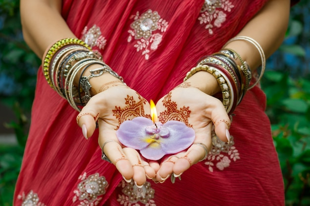 Красивая женщина в традиционных мусульманских индийских свадебных розовых сари одевает руки с татуировкой хной. украшения и браслеты с изображением менди держат горящую свечу лотоса.