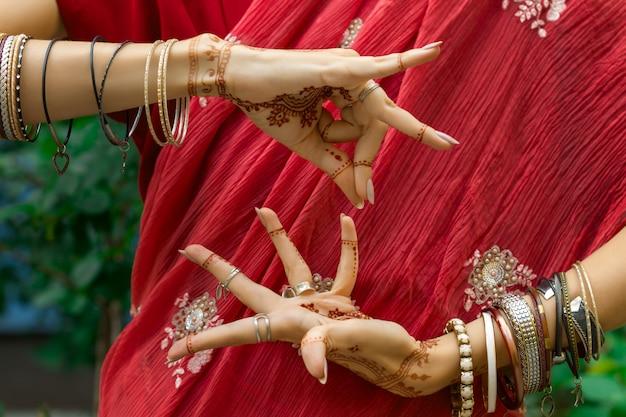 Красивая женщина в традиционном мусульманском индийском свадебном розовом платье сари с татуировкой хной и браслетами делают руки нритта одисси самюта хастас танец движение алападма брамара концепция фон