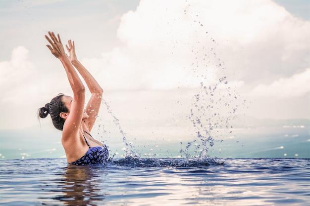 청록색 푸른 수영장에서 아름 다운 여자입니다.