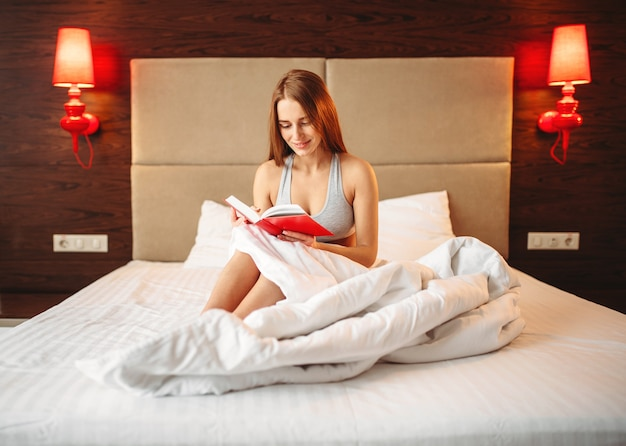 Красивая женщина в нижнем белье читает книгу в постели. девушка просыпается утром в спальне