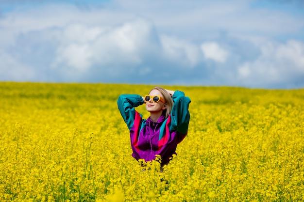 노란 유채 밭에서 빈티지 운동복에서 아름 다운 여자
