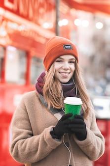 Красивая женщина в теплой одежде, стоя на зимней улице с бумажным стаканчиком кофе, на ярком уличном фоне