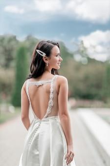 自然の背景にウェディングドレスの美しい女性