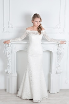 Красивая женщина в свадебном платье стоя возле декоративного камина. праздники и события