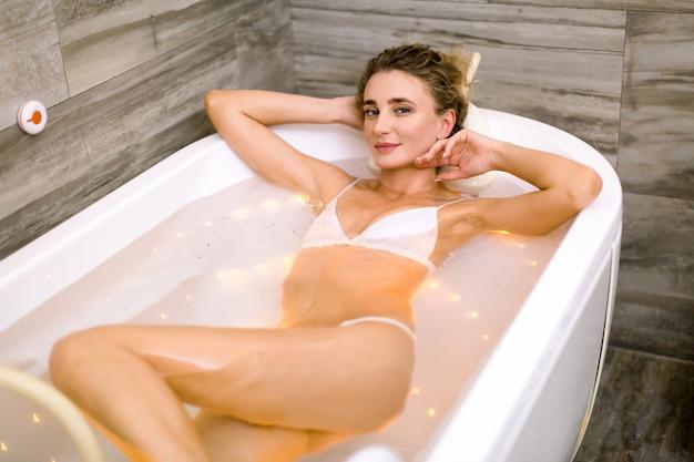 スパのジャグジー風呂で美しい女性。ハイドロマッサージバスでリラックスした白い水着で幸せな笑顔の女性