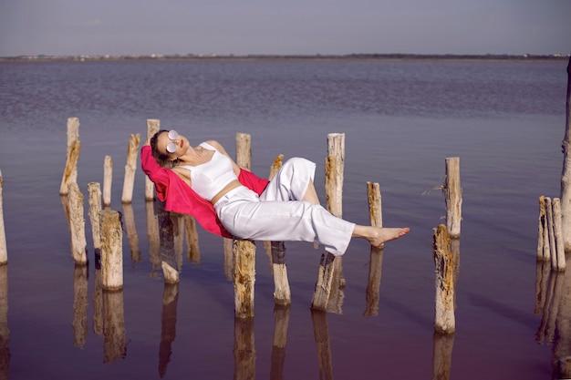 Красивая женщина в белой одежде и рубашке и солнцезащитных очках лежит