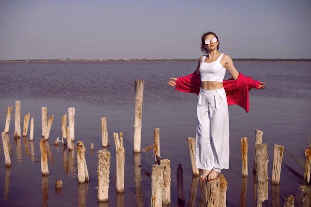 Красивая женщина в белой одежде и рубашке и солнцезащитных очках стоит