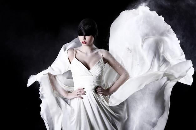白いドレスと空飛ぶほこりで美しい女性