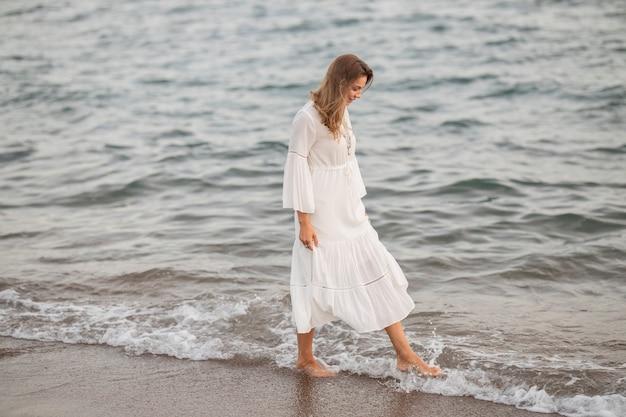 海のそばの白いドレスの美しい女性