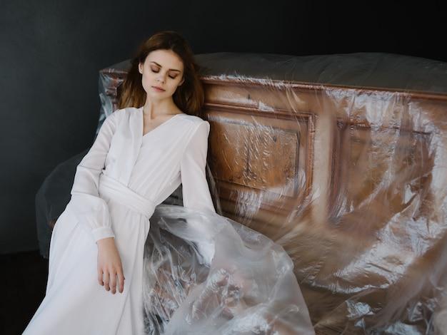 豪華なポーズのピアノに寄りかかって白いドレスの美しい女性
