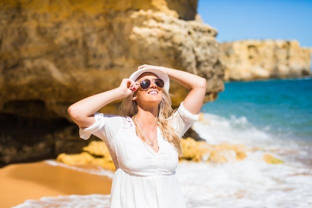 岩の多い海岸の白いドレスの美しい女性