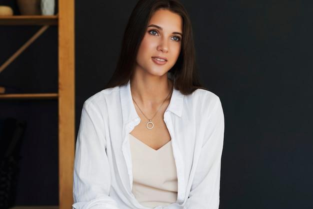 暗い壁に白いドレスシャツの美しい女性。黒髪の笑顔の女性の肖像画をクローズアップ。