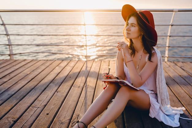 Красивая женщина в белом платье сидит у моря на восходе солнца, думая и делая заметки в дневнике