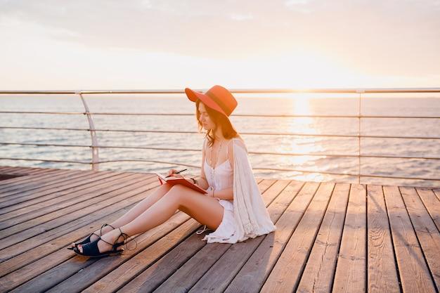 日の出の思考とメモを作ることで海に座っている白いドレスで美しい女性