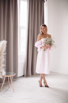 輝く大きな窓の近くに立っている白いドレスの美しい女性