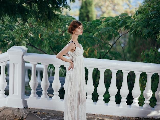 白いドレスの美しい女性伝統的なギリシャの服自然緑の葉