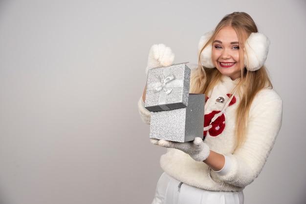 선물 상자 내부를 찾고 흰색 귀 따뜻한에 아름 다운 여자.