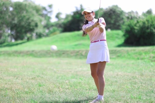 Красивая женщина в белой юбке, кепке и розовой футболке играет в гольф на зеленой лужайке