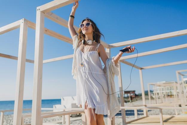 Красивая женщина в белом летнем платье слушает музыку в наушниках, танцует и веселится, держа смартфон, морской пляж в стиле летних каникул