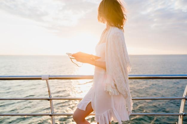 Красивая женщина в белом летнем платье гуляет по берегу моря на восходе солнца с дневником в романтическом настроении, думая и делая заметки